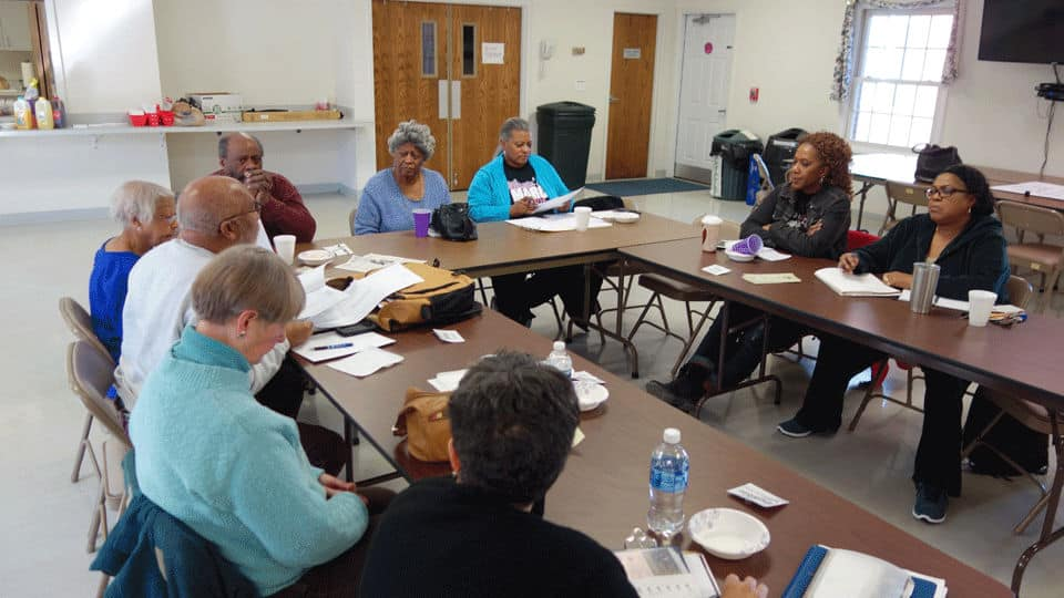 The Community Group gathers at its Annual Planning retreat around meeting tables